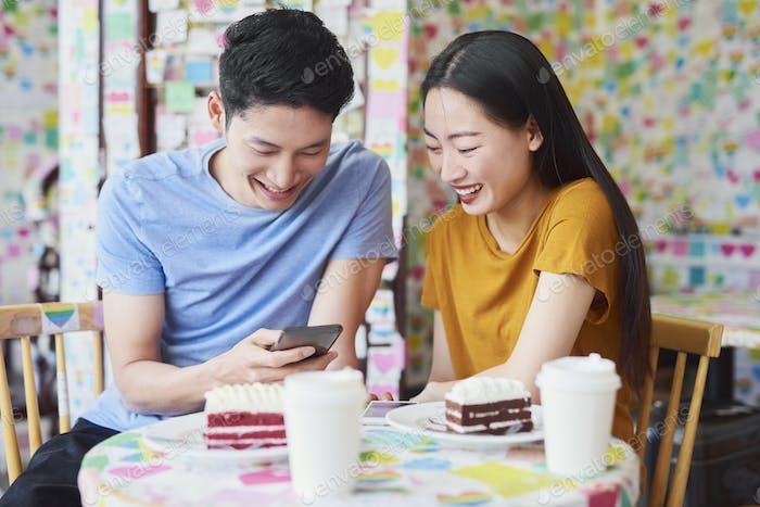 Vietnamesisches Paar genießen das kostenlose Internet in einem Café