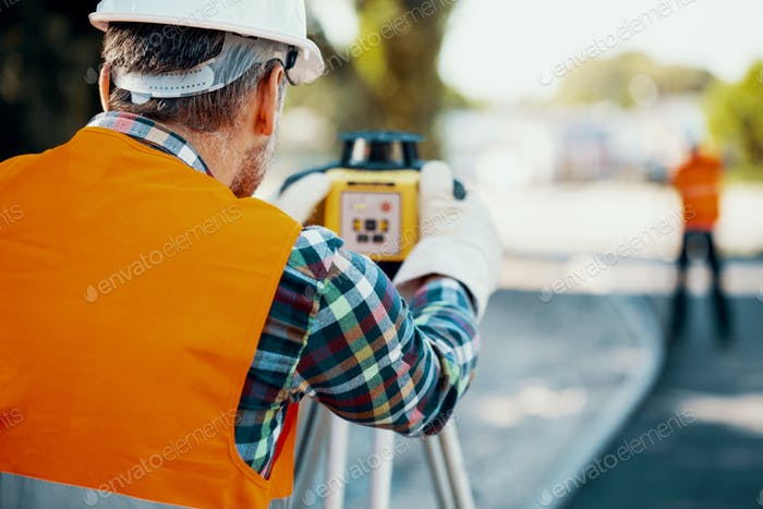 Geodesist in orange vest measuring with a total station