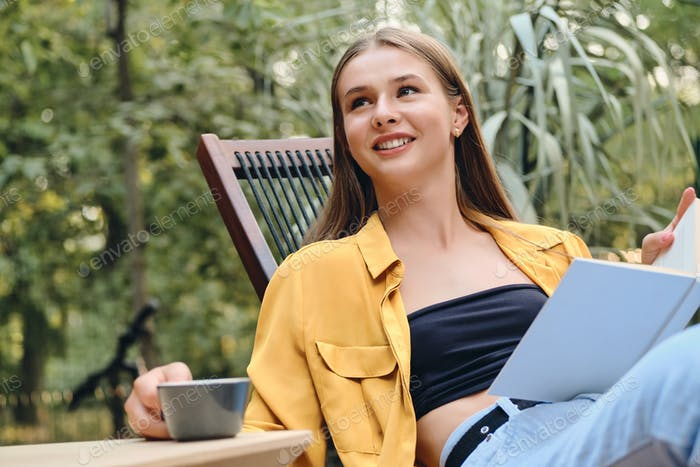 Young pretty teenage girl in yellow shirt and top happily drinking coffee and reading book in park
