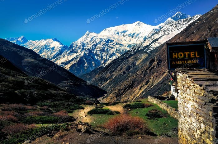 Mountain landscape view with local stone hut and hotel sign, Himalayas