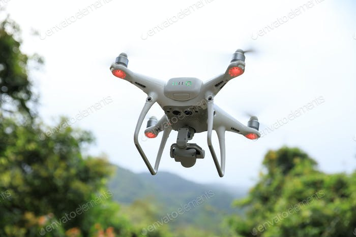 Drone with camera flying in tropical forest