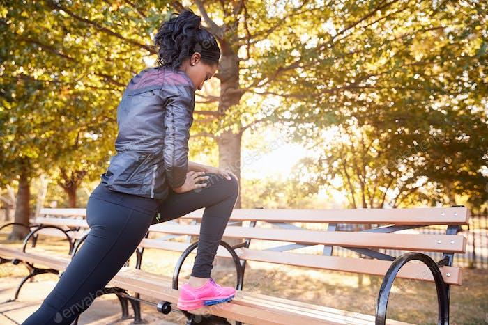 Junge schwarze Frau Stretching auf einer Bank in einem Brooklyn Park