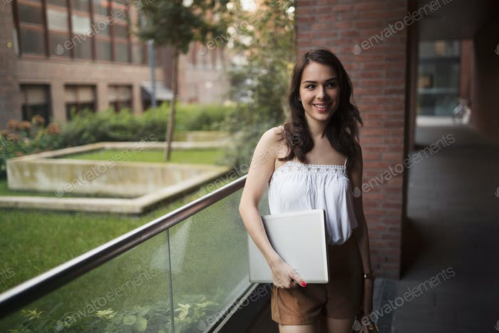 Portrait of young smiling woman holding laptop