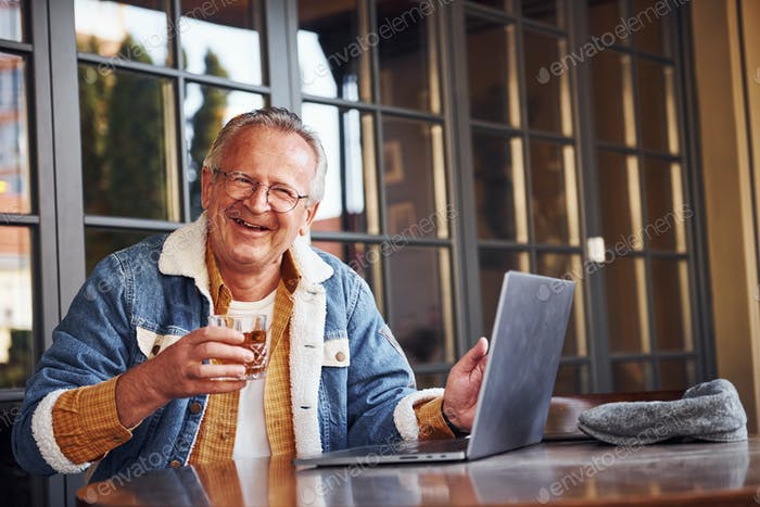 Stylish senior in fashionable clothes and in glasses sits in the cafe with drink in his hand