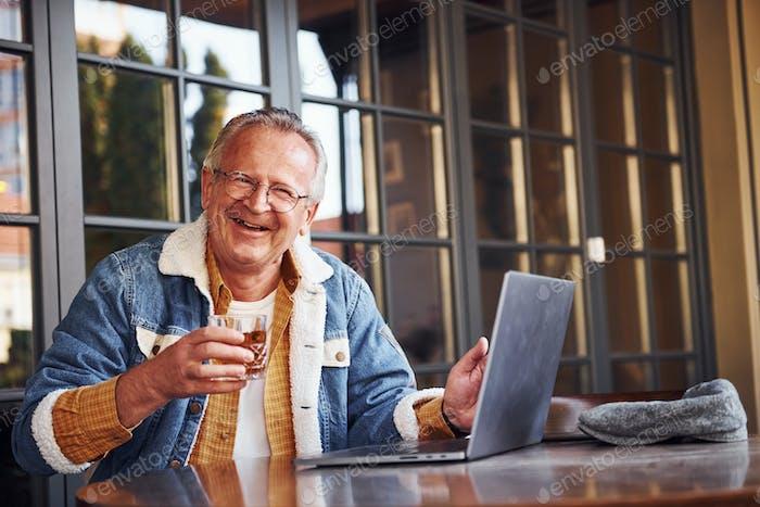 Stilvolle Senior in modischer Kleidung und in Gläsern sitzt im Café mit Getränk in der Hand