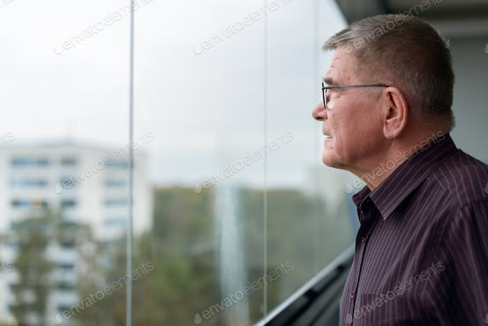 Profile view of old man thinking while looking outside glass window of modern building