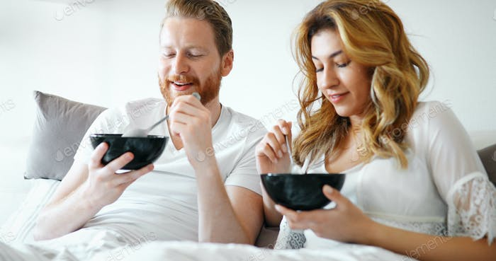 Young attractive couple having breakfast in bed