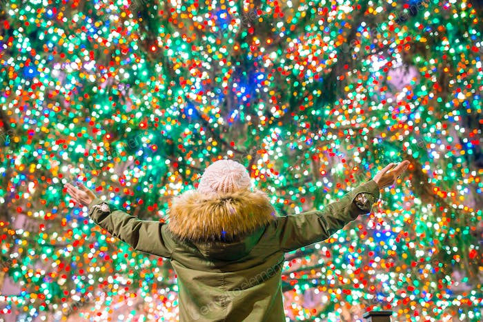 Happy girl on the background of the Rockefeller Christmas tree in New York