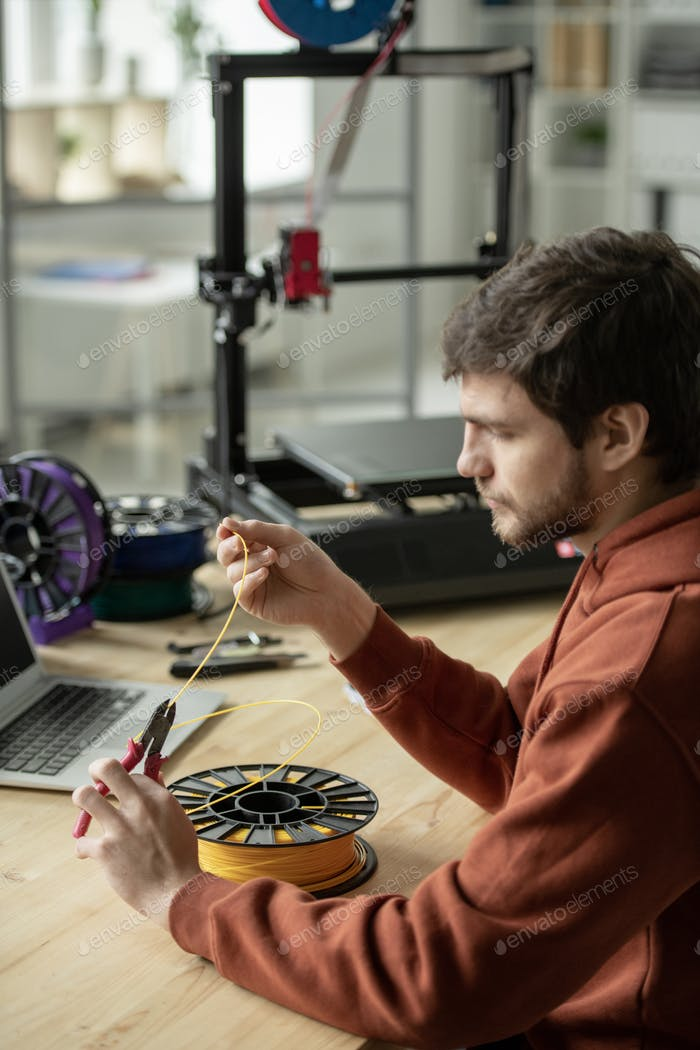 Creative man sitting by table and cutting piece of yellow filament for printing
