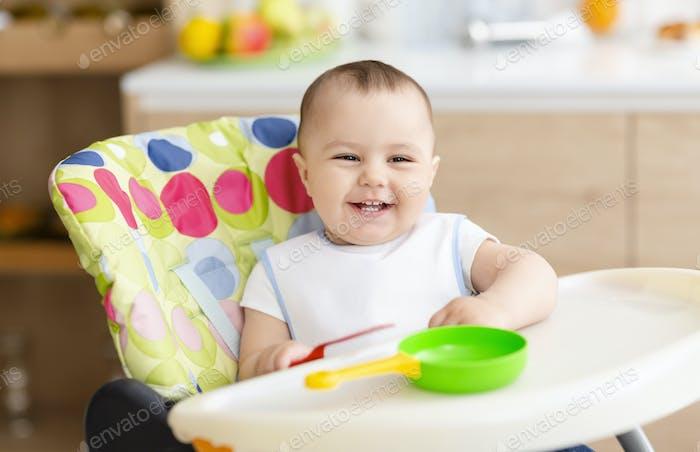 Cheerful infant sitting in high children chair toys in kitchen