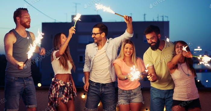 Freunde genießen Dachterrasse Party mit Wunderkerzen
