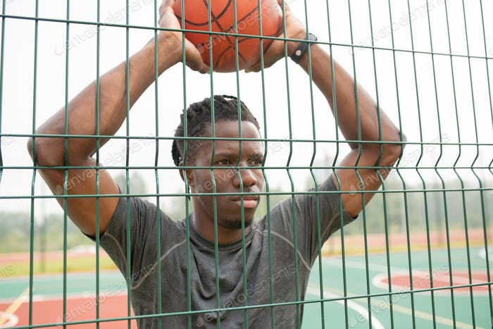 Young basketball player of African ethnicity holding ball over his head