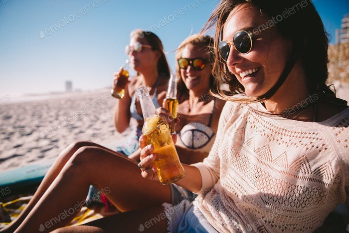 friends cheering with beer at the beach celebrating