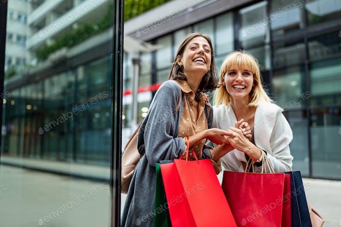 Schöne glückliche Frauen mit Einkaufstaschen zu Fuß in der Mall