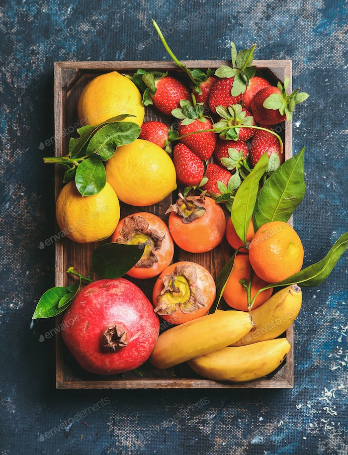 Oranges, lemons, pomegranate, bananas, strawberries and persimmon in wooden box