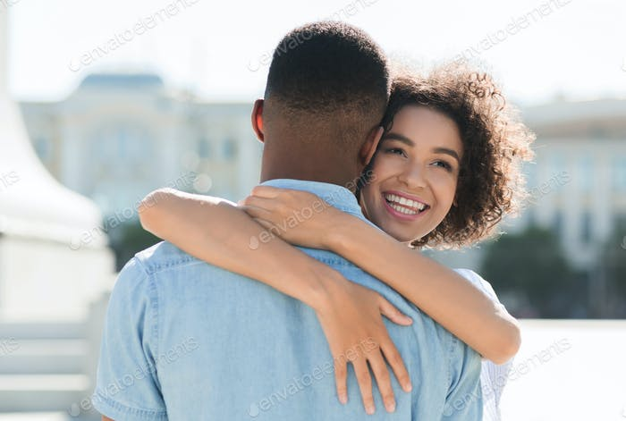 Portrait of happy couple hugging in the street