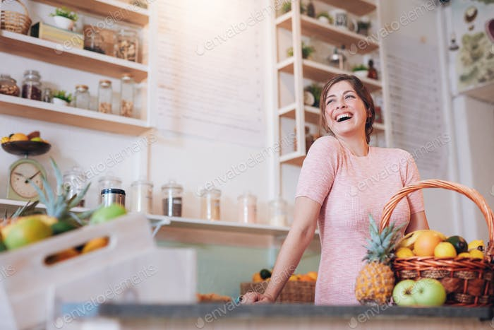 Smiling woman standing at a juice bar counter