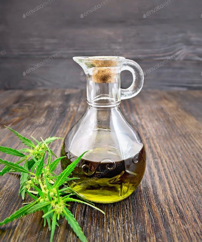 Öl Hanf in Glas Dekanter auf dunklem Brett