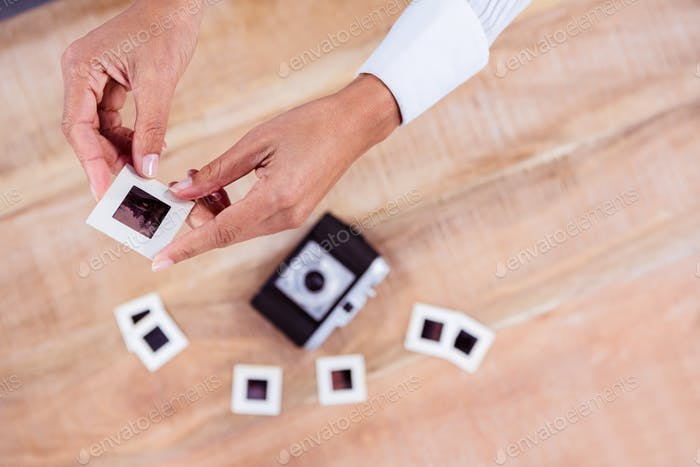 View of hands holding photo slides against wooden plank
