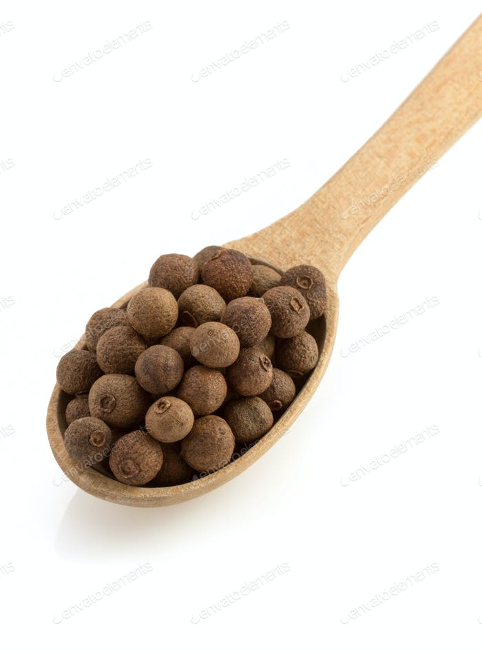 allspice in spoon on white