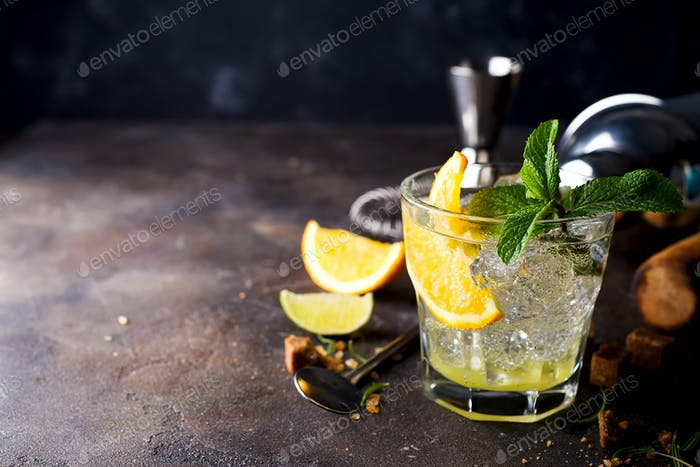 Refreshing cold alcoholic summer citrus cocktail with orange, peppermint and crushed ice in glasses