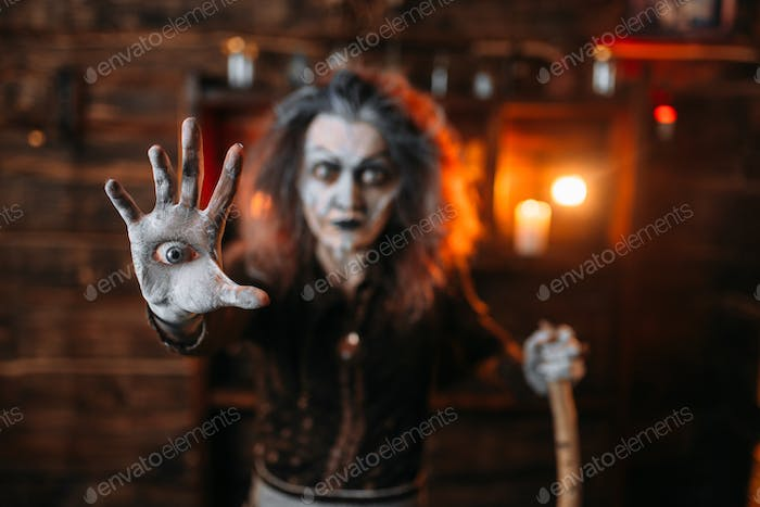 Scary witch with an eye in the palm, seance