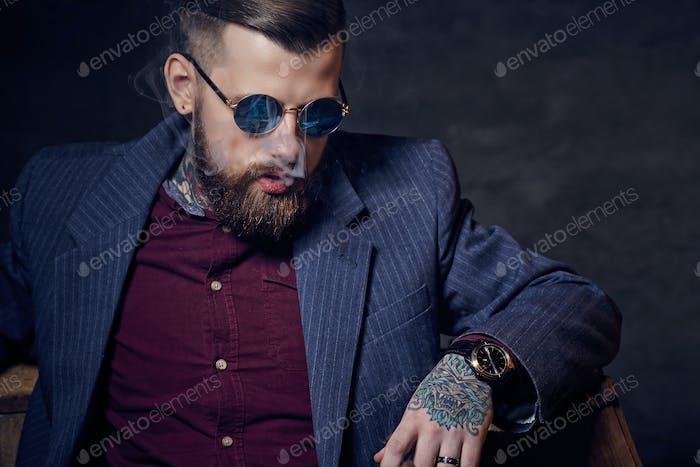 A man in sunglasses smoking a cigar.