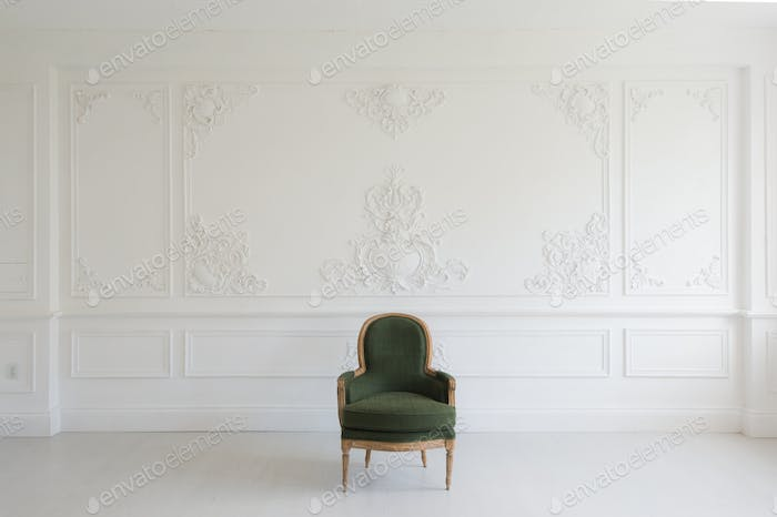 Living room with antique stylish green armchair on luxury white wall design bas-relief stucco