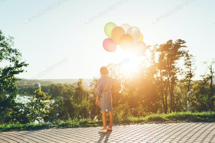 Cute girl holding colorful balloons in the city park dreaming