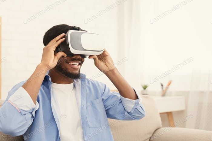 Cheerful man trying vr glasses at home