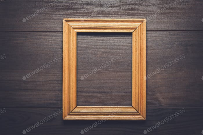old empty frame over wooden background