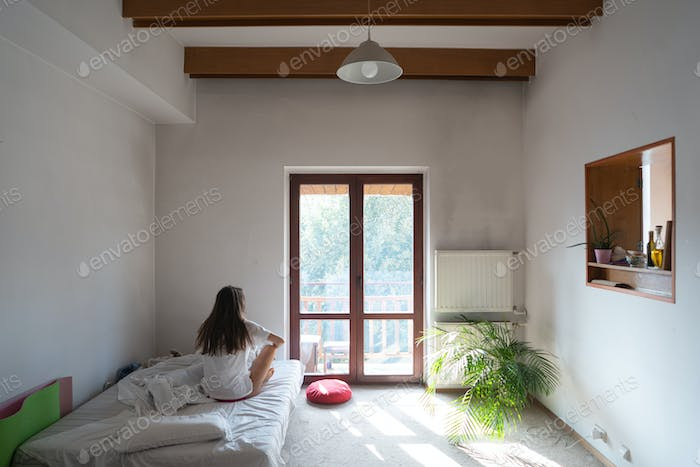 Young woman sitting on bed and looking through the window