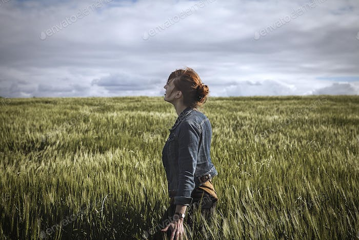 Woman in Jean Jacket Walking Through Grassy Field