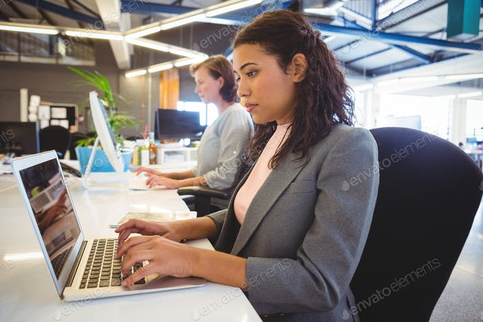 Woman sitting at desk and working on laptop