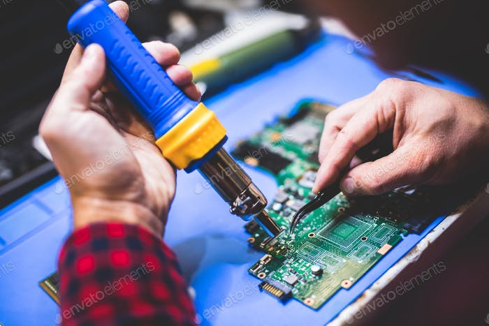 Человек, фиксирующий главную плату компьютера.