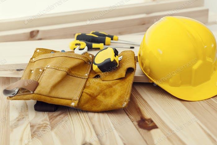 Holztisch mit Werkzeugen und Helm