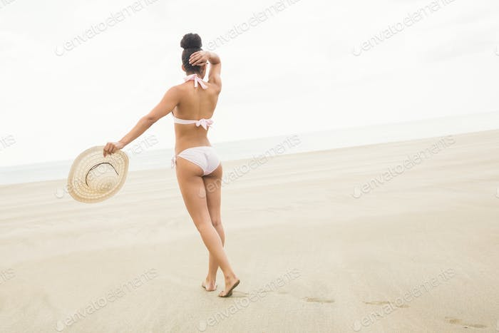 Fit Frau im Bikini zu Fuß zum Meer am Strand