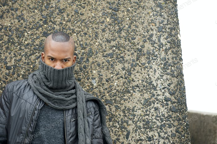 Black man with scarf covering face outdoors