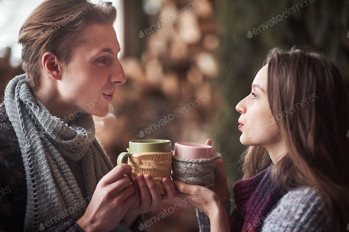Photo of happy man and pretty woman with cups outdoor in winter. Winter holiday and vacation