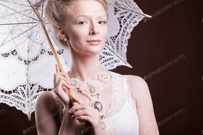 Portrait of woman in vintage dress holding a lace umbrella