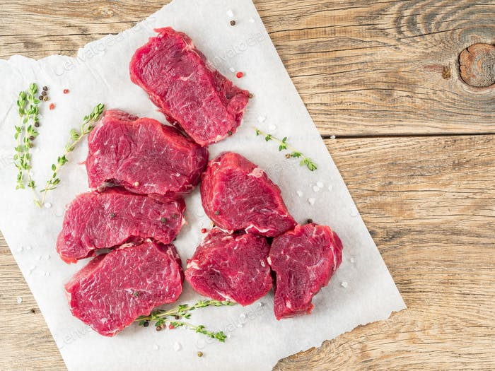 Pieces of raw meat. Raw beef with spices and thyme