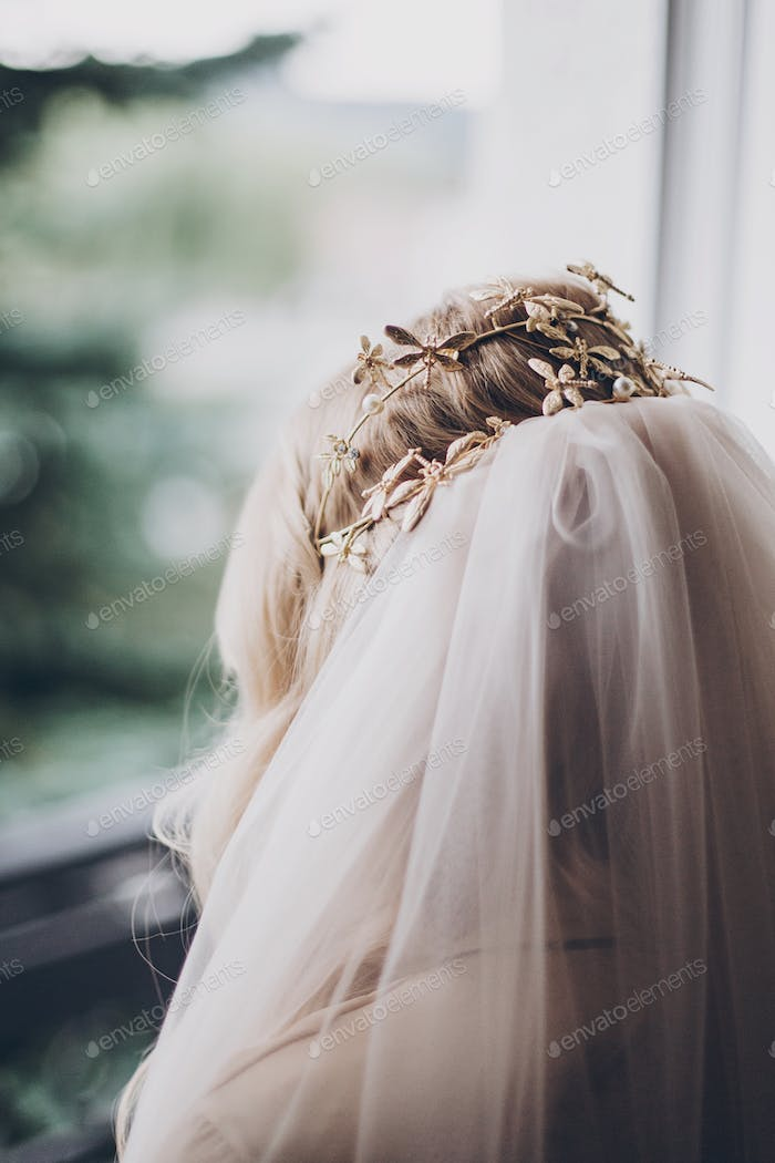Stylish bride with golden tiara with butterflies and veil