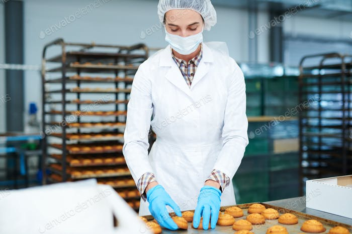 Confectioner collecting freshly baked pastry from tray