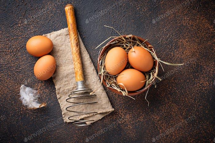 Frische braune Eier in Schüssel und Schneebesen