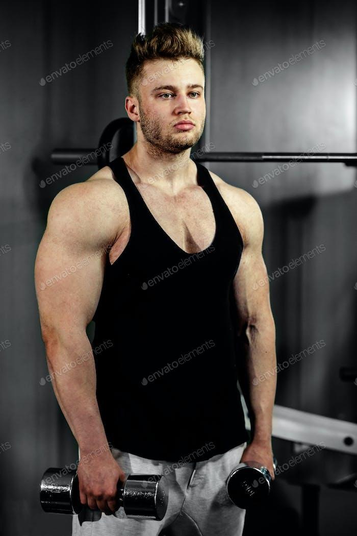 сильный красивый культурист спортсмен работает с гантелями в тренажерном зале