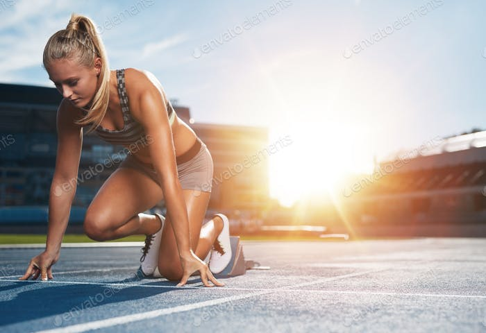 Female sprinter in track starting blocks