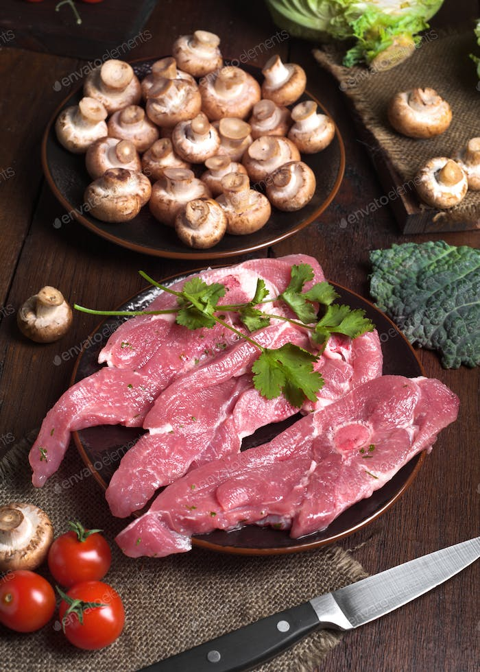 turkey fillets raw mushrooms and other vegetables, on classic wooden board