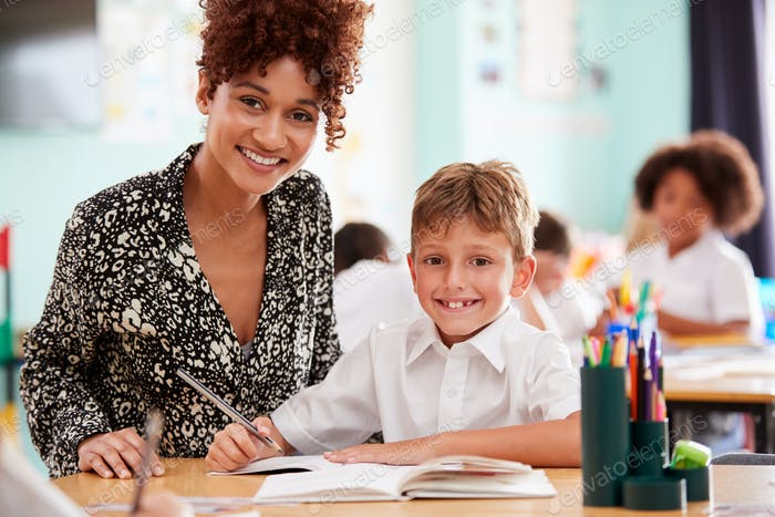 Portrait Of Woman Elementary School Teacher Giving Male Pupil Wearing Uniform One To One Support