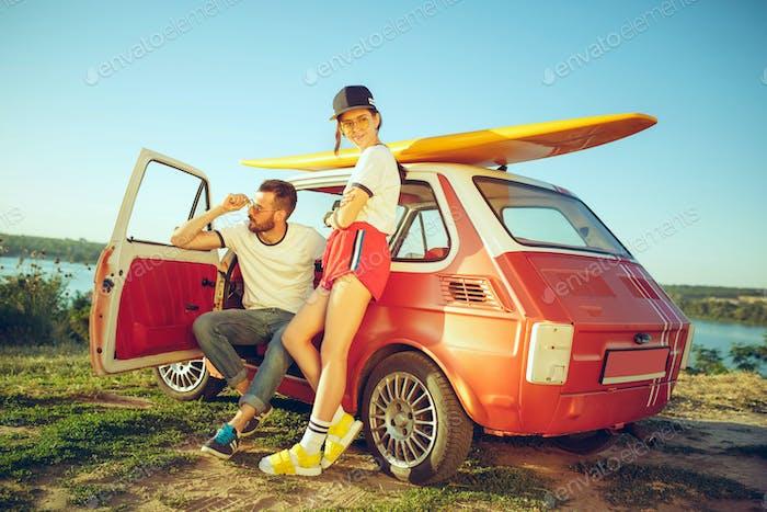 Пара отдыхает на пляже в летний день возле реки