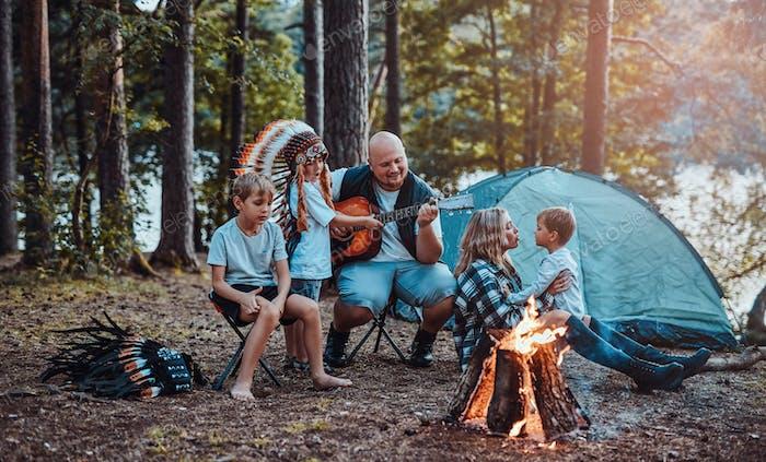 Familia alegre de Estados Unidos descansando cerca de la fogata